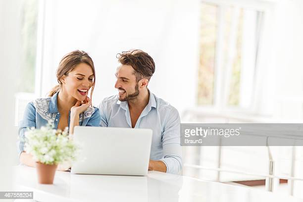 Young cheerful couple using laptop at home.