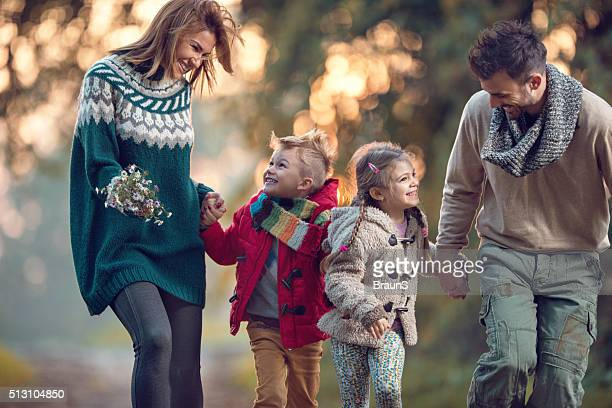 Young cheerful family running in the park and having fun.