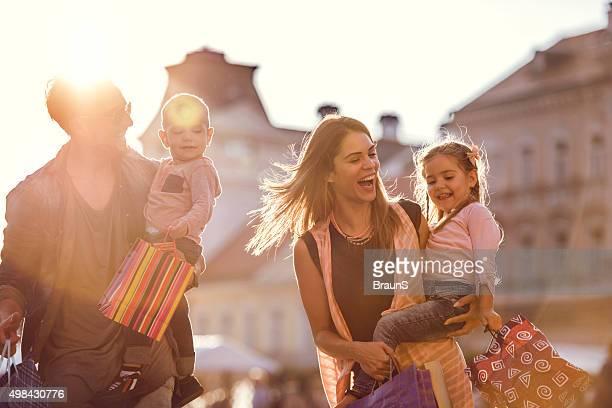 Junge freudig Familie einkaufen in der Stadt bei Sonnenuntergang.