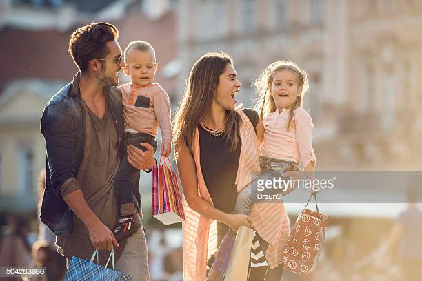 Young cheerful family shopping together in the city.