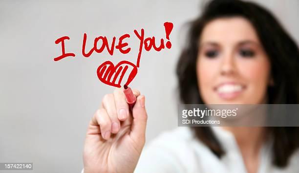 "Young Cheerful Girl Writing ""I Love You"""