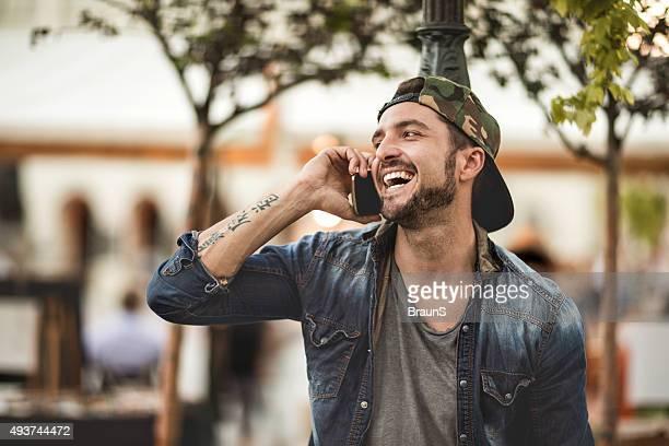 Junge fröhlich Mann spricht sich jemand auf Handy.