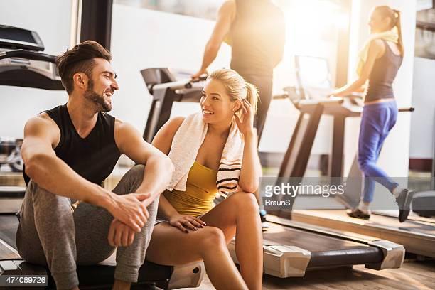 Giovane allegro persone a riposo da esercizio in palestra e la comunicazione.