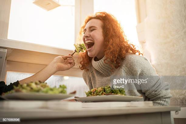 Young cheerful woman being fed by unrecognizable man.