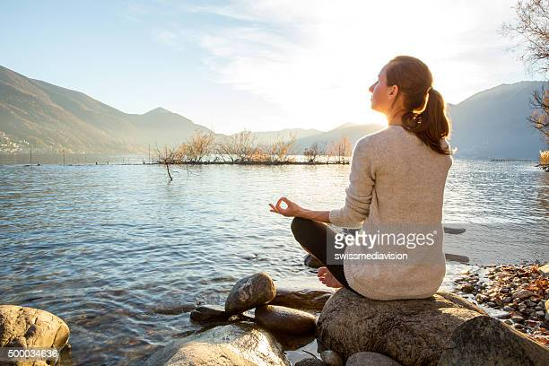 Young cheerful woman by the lake exercising yoga at sunset