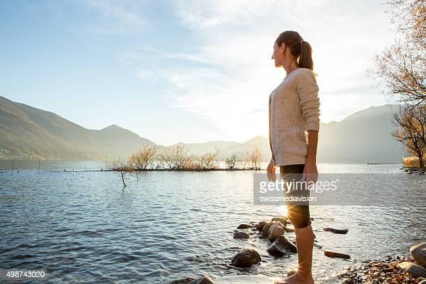 若い女性が明るく、湖の夕日