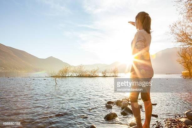 Jeune femme joyeuse en regardant le coucher de soleil sur le lac