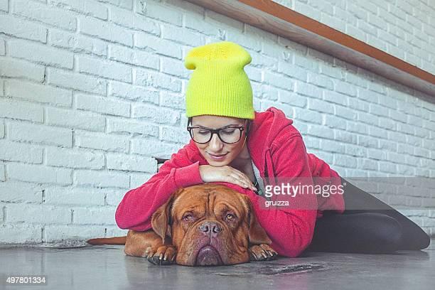 Junge fröhliche Frau umarmen Ihr sleepy Hund