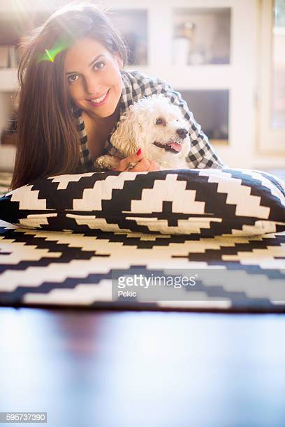 Young cheerful woman having fun with her dog