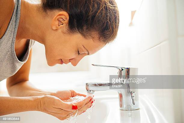 Young cheerful woman having morning hygiene in bathroom