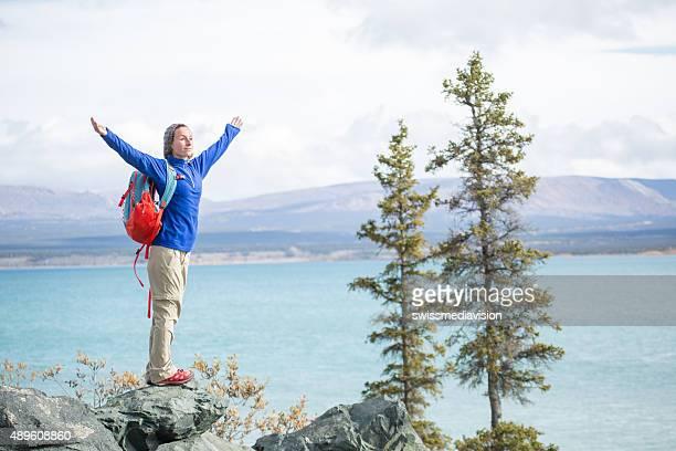 """Jeune femme joyeuse la randonnée par le lac de profiter de la nature """"."""