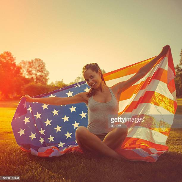 Young cheerful woman holding an american flag