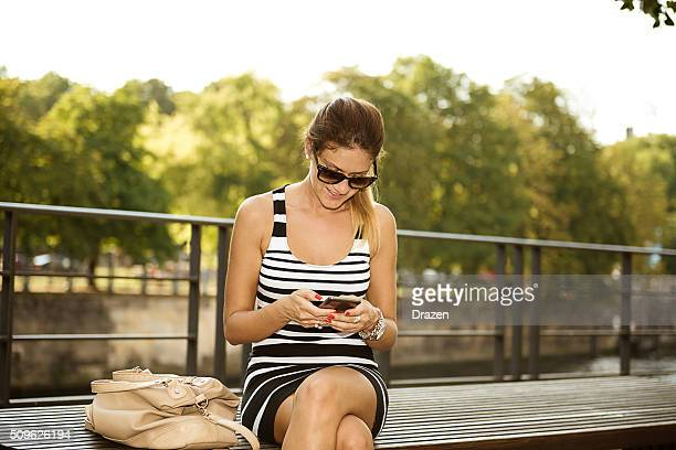 Junge fröhliche Frau im Kleid mit Smartphone in der Nähe vom Alexanderplatz in Berlin