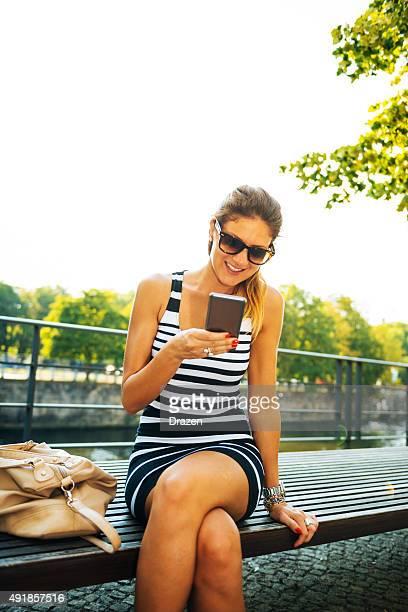 Junge fröhliche Frau im Kleid mit smartphone in der Nähe der berühmten Wahrzeichen