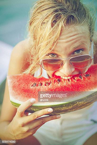 Young cheerful woman on the pier biting juicy watermelon
