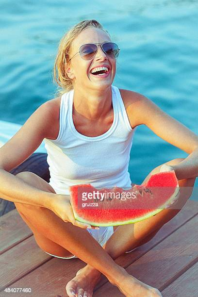 Young cheerful woman sitting on boat dock and holding watermelon