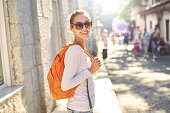 young cheerful woman with small orange packpack walking on the street at summer day