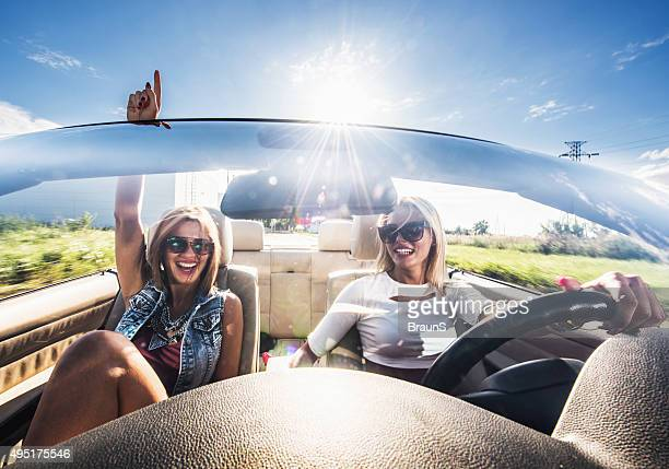 Young cheerful women enjoying while driving cabriolet during sunny day.