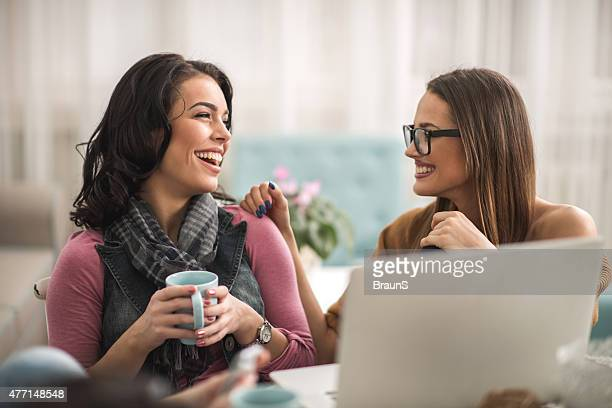 Young cheerful women talking to each other at home.