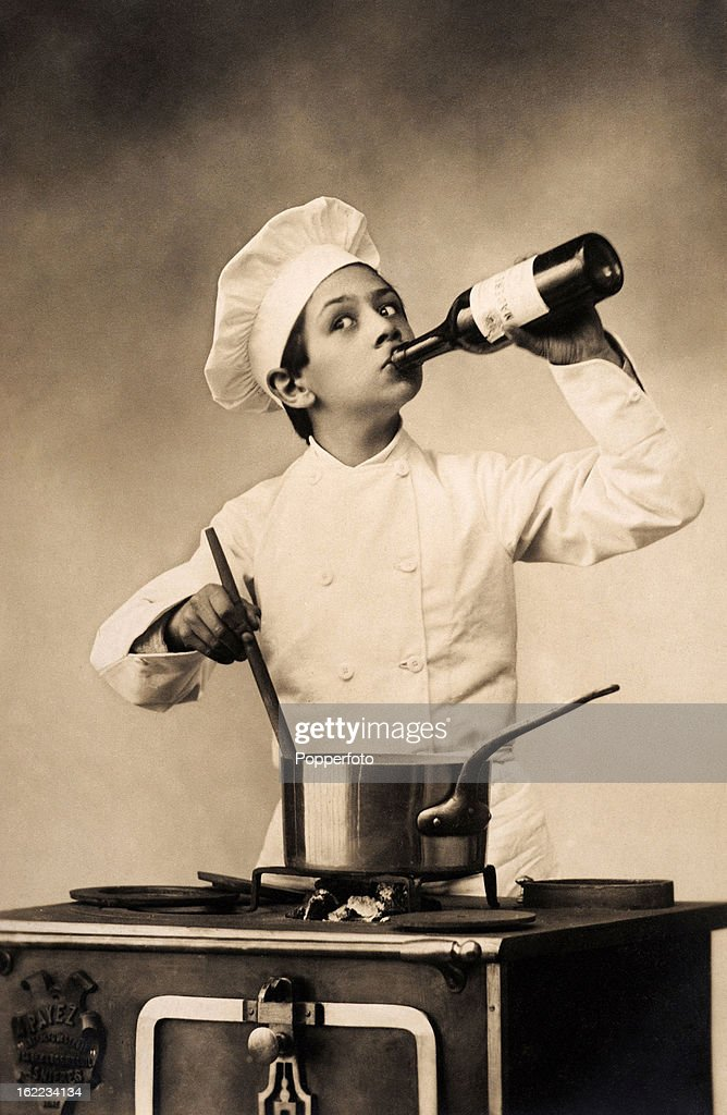 A young chef drinking on the job, imbibing a bottle of wine whilst stirring the pot, circa 1920.