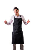 Young chef or waiter posing, wearing black apron and shirt isolated on white background, holding empty space between hands