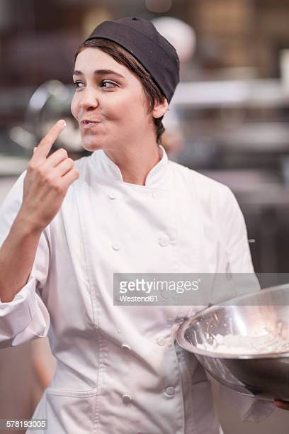 Young chef tasting dough with finger