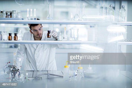 Young chemist choosing the right bottle in a laboratory.
