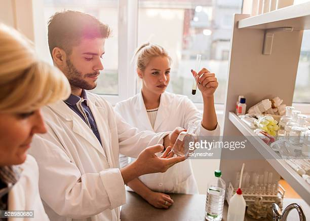 Young chemist working in laboratory with his colleagues.