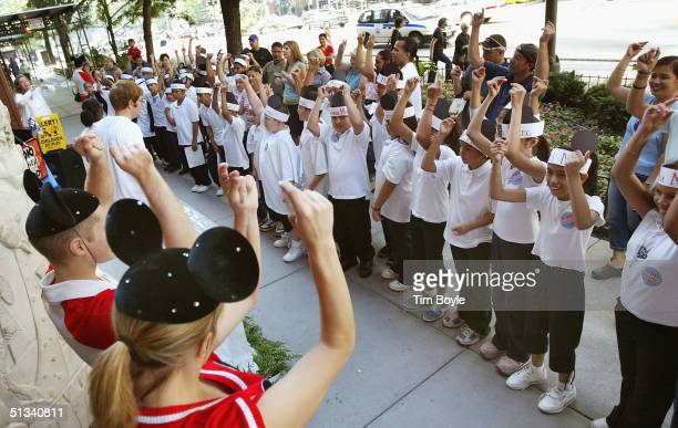 Young Chicago school students participate in a Mickey Mouse Club theme singing contest outside the Disney Store September 23 2004 in Chicago The...