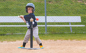 A young boy focuses on a baseball atop a tee during a baseball game.