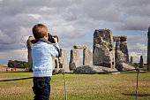 Young child, boy, taking pic with digital camera at Stonehenge on a cloudy day