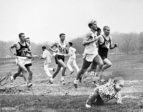 A young child crawls by the side of a cross country race course as runners pass by Cobbs Creek Pennsylvania 1968