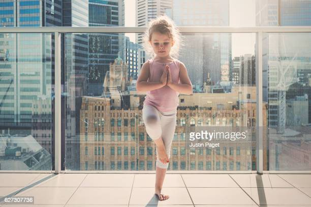 Young Child doing yoga with city backdrop