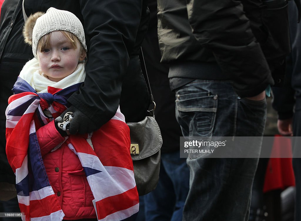 A young child drapped in the British Union flag stands with loyalist protesters during a demonstration outside Belfast City Hall in Belfast on January 12, 2013 as part of an ongoing campaign opposing Belfast City Council's decision to restrict the days on which the British Union Flag will fly over the City Hall. Northern Irish demonstrators loyal to Britain clashed with nationalists and police on Saturday in fresh protests against curbs on flying the British flag, leaving four officers injured, police said. Pro-British demonstrators have taken to the streets, in sometimes violent protest, almost every night since December 3, when the city council announced it would no longer fly the Union Flag all year round at City Hall.
