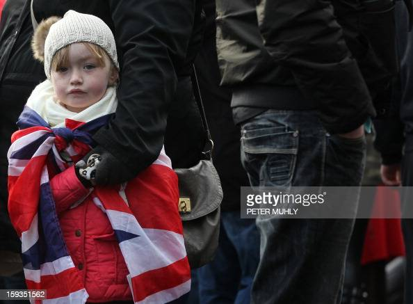 A young child drapped in the British Union flag stands with loyalist protesters during a demonstration outside Belfast City Hall in Belfast on...