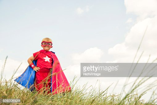 Young Child Dressed as Superhero in Tall Grass