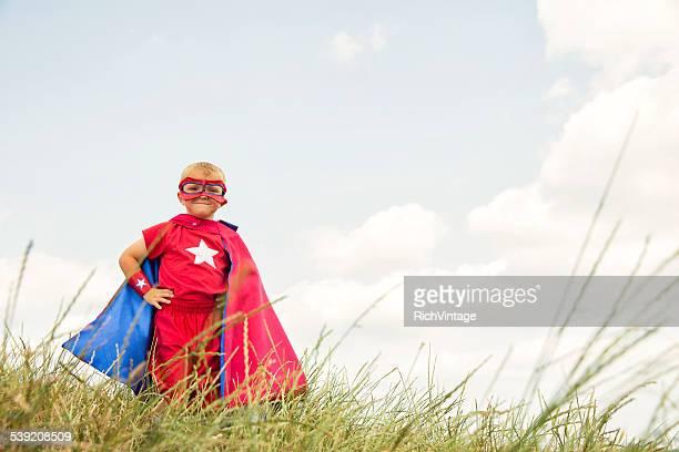 Junge Kind angezogen wie Superhelden im hohen Gras