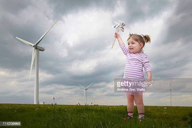young child holding windmill near wind turbines