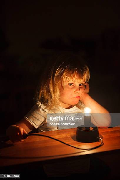Young child, illuminated by bare bulb