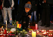 A young child lays a flower at the Place de la Bourse following today's attacks on March 22 2016 in Brussels Belgium At least 31 people are thought...