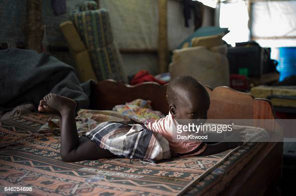 A young child lays on a bed in a tent set up to look after orphaned and unaccompanied children on February 25 2017 in Palorinya Uganda The continued...