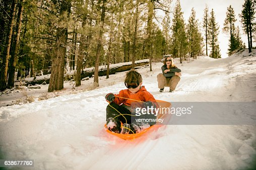 young child learning to sled with mom watching