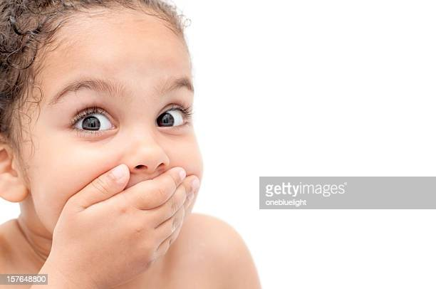 Young child looking surprised and covering mouth with hand