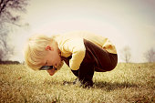 A young child is bending down looking in the grass, investigating something with a magnifying glass.  Vintage style color.