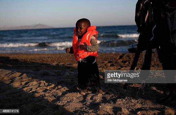 A young child migrant from Gambia cries after safely completing a journey with his mother across a three mile stretch of the Aegean Sea in a small...