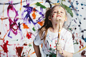 Young child painter standing with a brush in front of a messy background. Creativity.