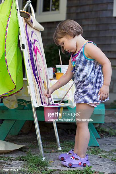 Young child painting at easel
