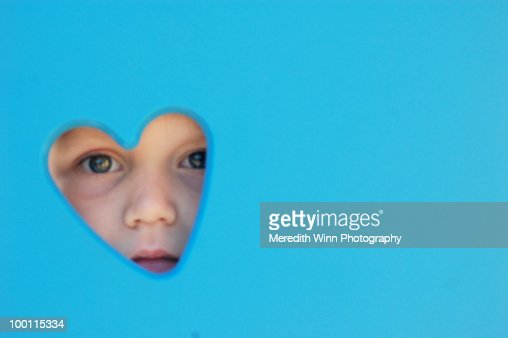 Young child peeking through a heart shape : Foto de stock
