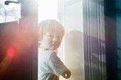 young child peeking through door