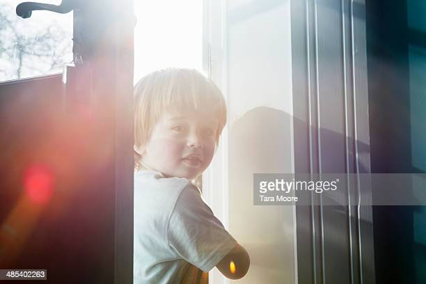 young child peeking through door